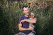 Handsome young man holding and hugs a yorkshire terrier dog