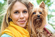 Close up portrait smiling young blonde with yorkshire terrier ou